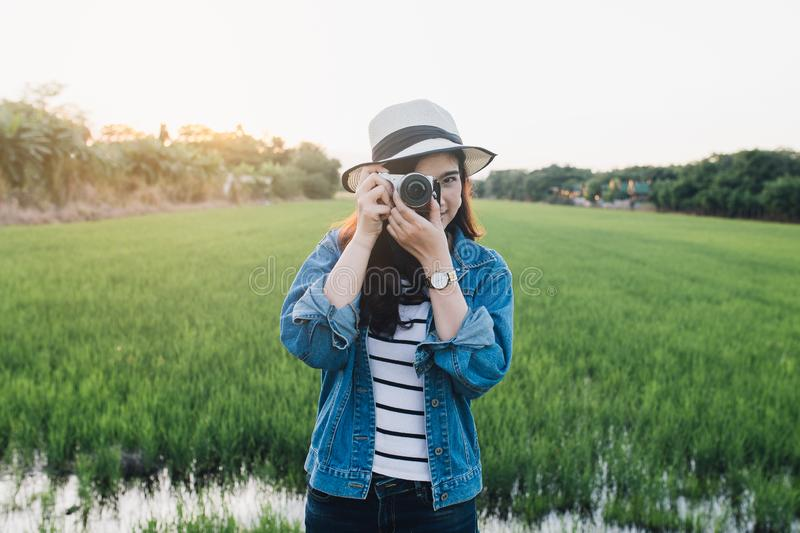 Young asian woman smiling in hat with camera. Girl enjoying at beautiful nature with sunset. Travel Summer Holiday Vacation royalty free stock image