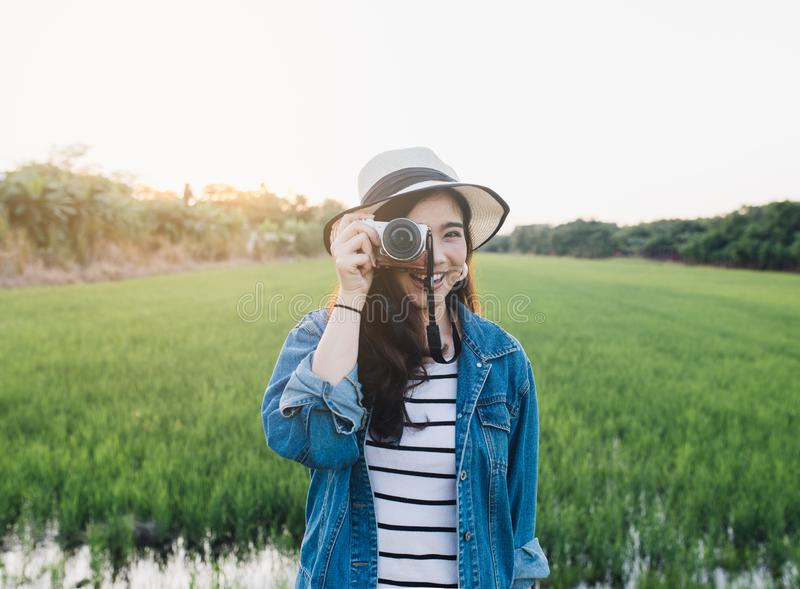Young asian woman smiling in hat with camera. Girl enjoying at beautiful nature with sunset. Travel Summer Holiday Vacation stock photos