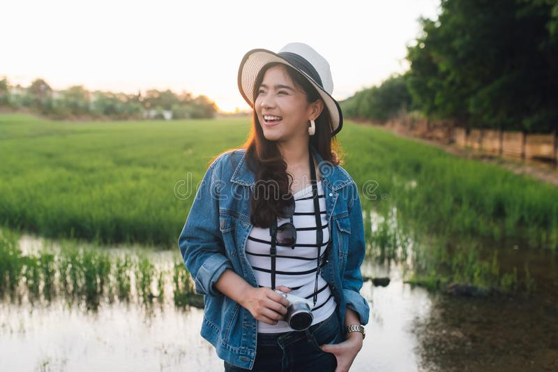Young asian woman smiling in hat with camera. Girl enjoying at beautiful nature with sunset. Travel Summer Holiday Vacation stock photo