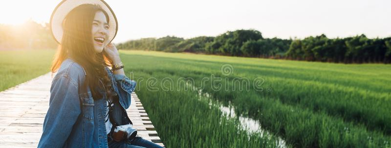 Young asian woman smiling in hat. Girl enjoying at beautiful nature with sunset. Travel Summer Holiday Vacation and Relaxation royalty free stock photography