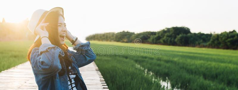 Young asian woman smiling in hat. Girl enjoying at beautiful nature with sunset. Travel Summer Holiday Vacation and Relaxation stock photos