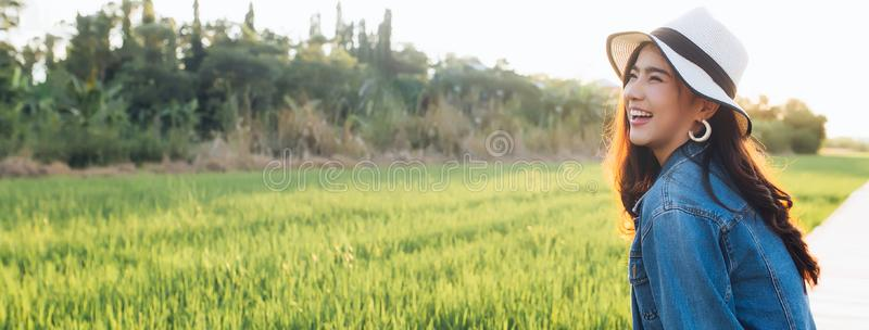 Young asian woman smiling in hat. Girl enjoying at beautiful nature with sunset. Travel Summer Holiday Vacation and Relaxation royalty free stock images