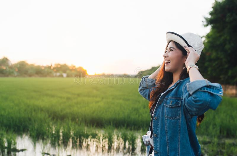 Young asian woman smiling in hat. Girl enjoying at beautiful nature with sunset. Travel Summer Holiday Vacation and Relaxation stock images