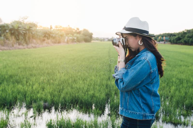 Young asian woman smiling in hat. Girl using camera and enjoying at beautiful nature with sunset. Travel Summer Holiday Vacation royalty free stock images