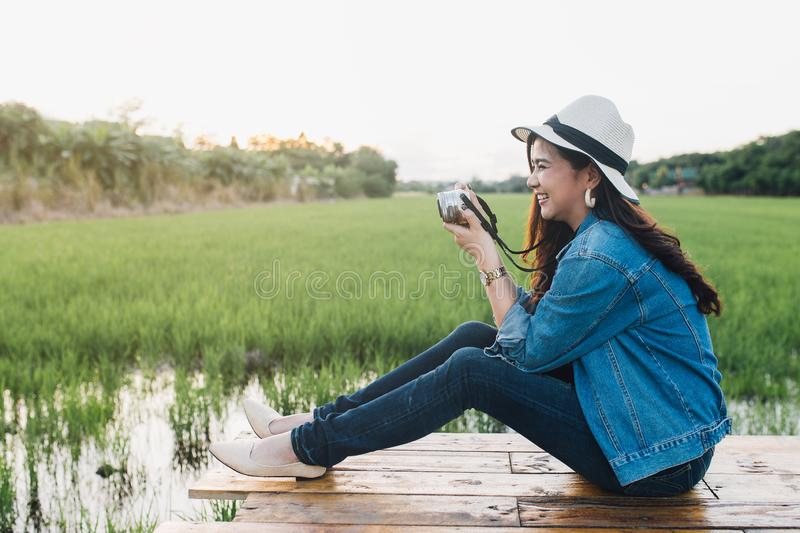 Young asian woman smiling in hat. Girl using camera and enjoying at beautiful nature with sunset. Travel Summer Holiday Vacation stock photography