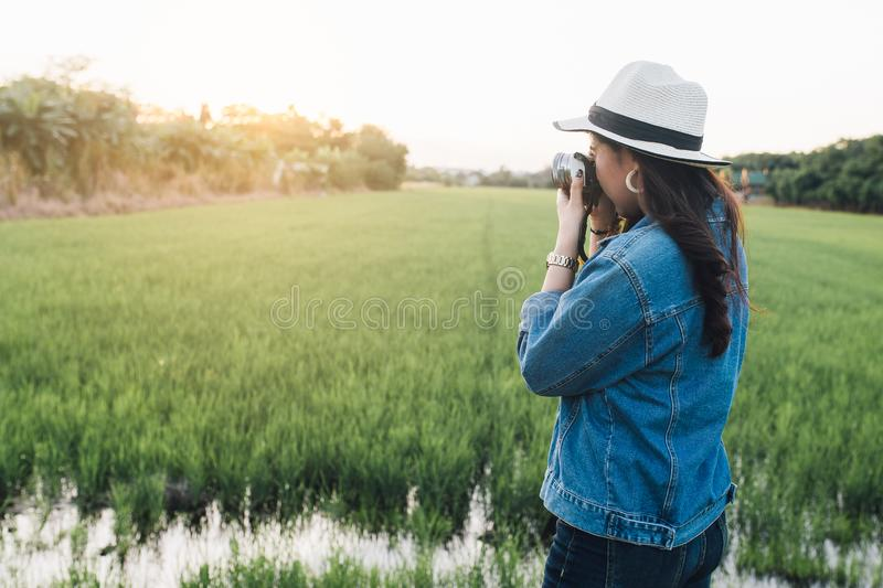 Young asian woman smiling in hat. Girl using camera and enjoying at beautiful nature with sunset. Travel Summer Holiday Vacation royalty free stock photography