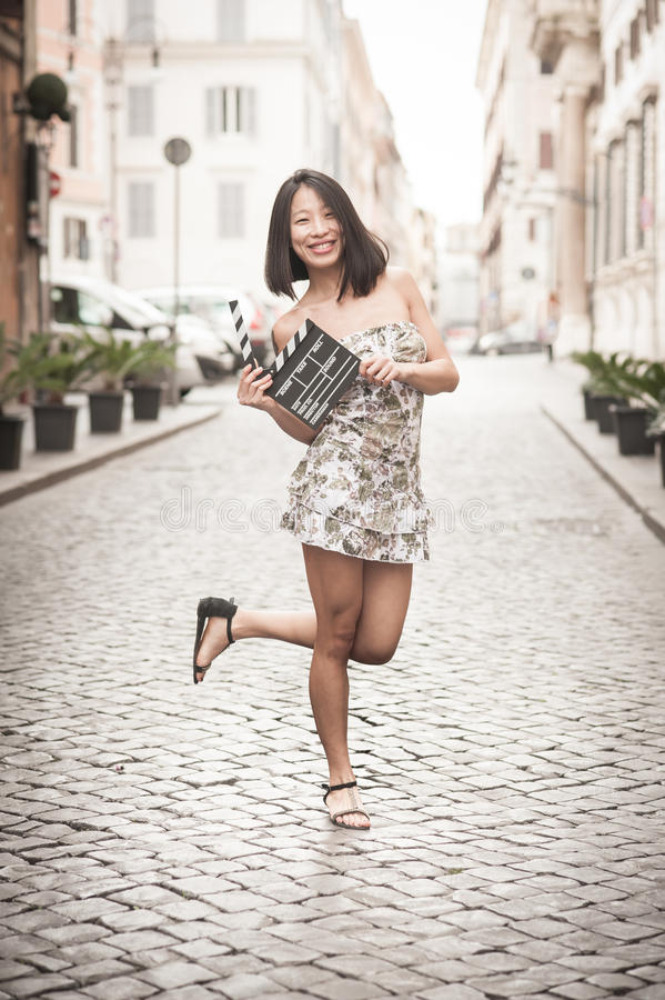 Young asian woman smiling and showing clapperboard urban scene stock photo