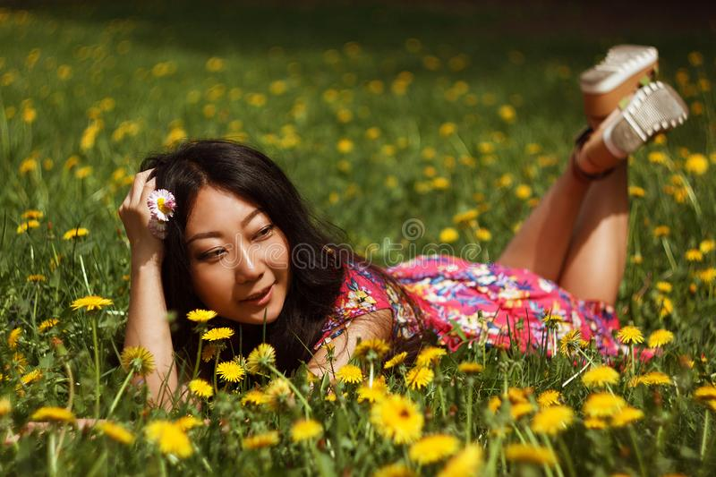 Young happy asian woman in the field with dandelions in the meadow a sunny day. Young asian woman smilling in the green field with dandelions in the meadow a stock image