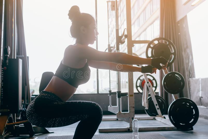Young asian woman in sportswear doing squat at heath indoor gym. Young asian woman in sportswear doing squat at heath indoor gym royalty free stock photos