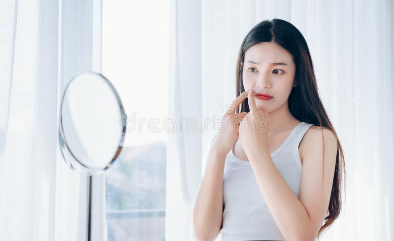 Young Asian woman squeeze acne problem face stock photography