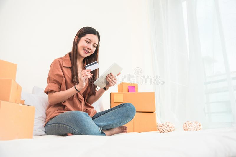 Young Asian woman startup small business entrepreneur SME distribution warehouse with parcel mail box. Owner home office. Online stock photography