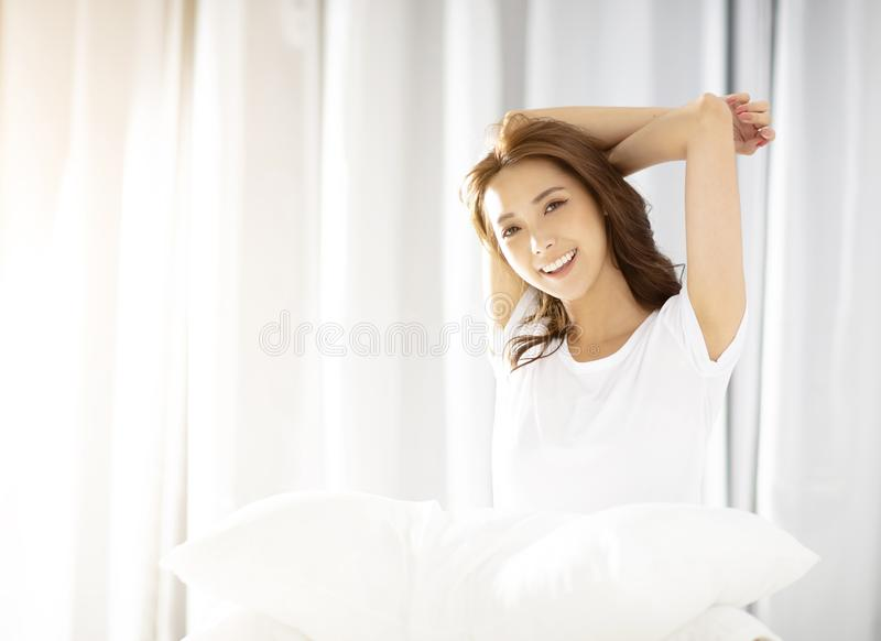 Young Woman stretching in bed after wake up stock photos