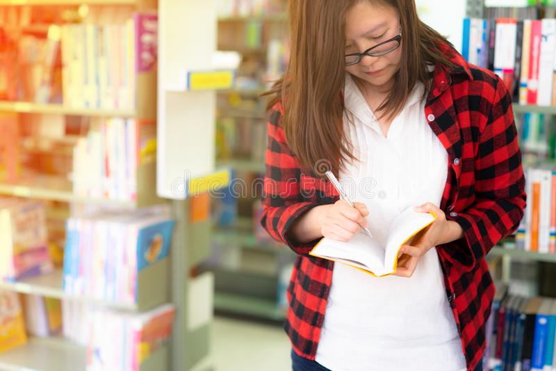 Young asian woman student in the library reading a book royalty free stock photography