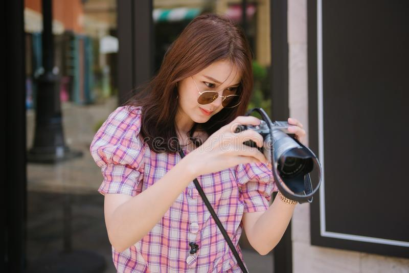Young asian woman checking photos on her camera standing at street in the city. stock images