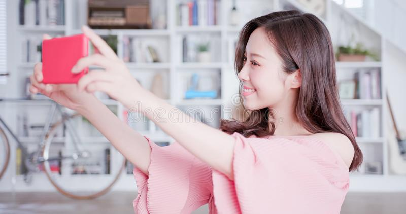 Young asian woman take selfie. Young asian woman take a selfie by smart phone at home royalty free stock photo