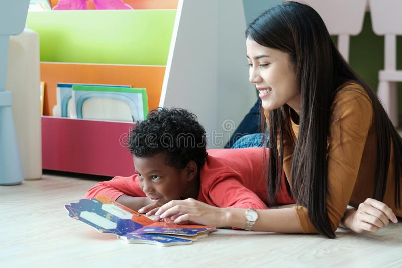 Young asian woman teacher and African boy in kindergarten classroom, preschool, elementary education concept royalty free stock photo