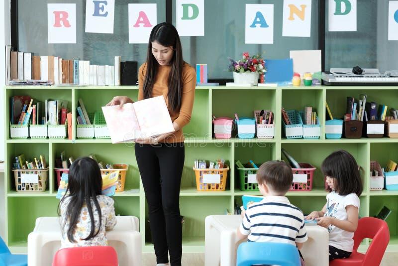 Young asian woman teacher teaching kids in kindergarten classroom, preschool education concept royalty free stock photo