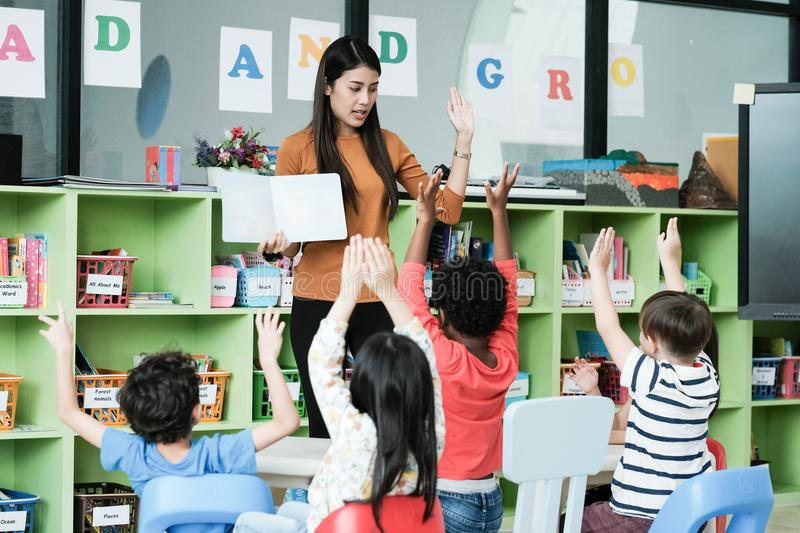 Young asian woman teacher teaching kids in kindergarten classroom, preschool education concept royalty free stock photography