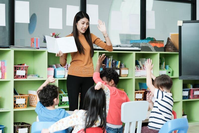 Young asian woman teacher teaching kids in kindergarten classroom, preschool education concept stock photography