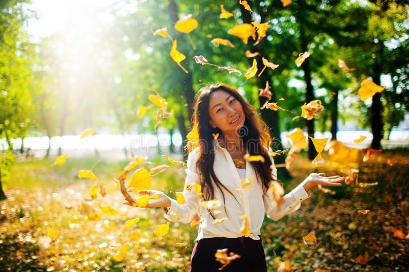 Young asian woman throwing autumn leaves in the air in the park stock image