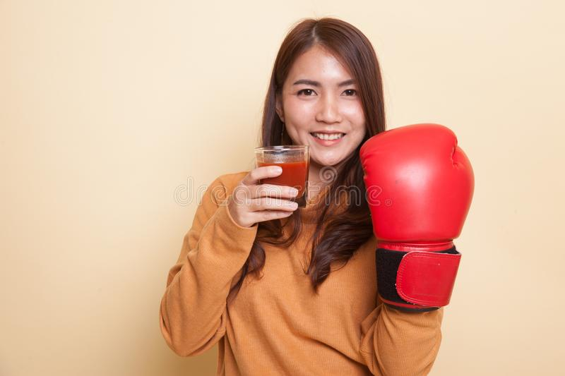 Young Asian woman with tomato juice and boxing glove. royalty free stock photo