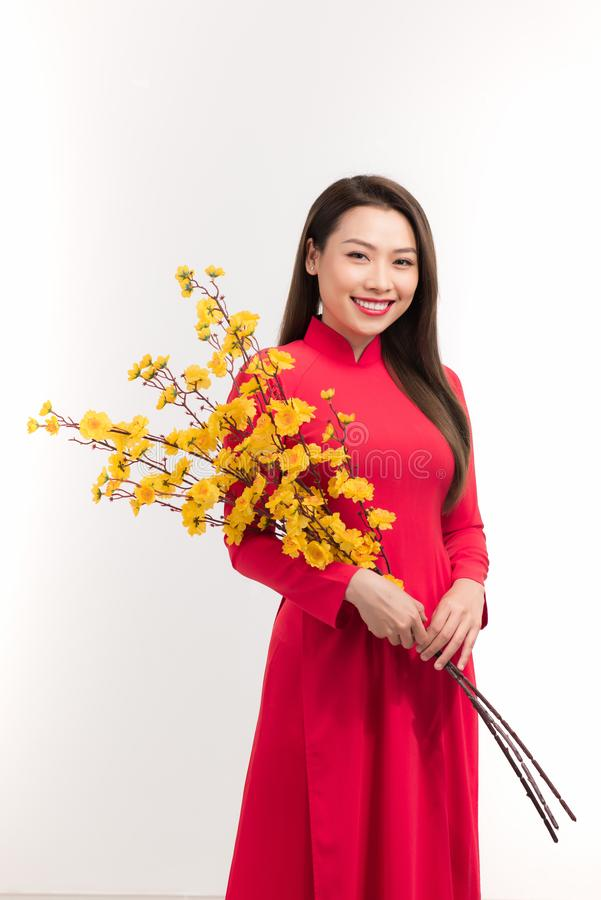 Young Asian woman in traditional aodai dress holding Hoa Mai tree Ochna Integerrima flower, smiling, celebrating Lunar New Year royalty free stock photography