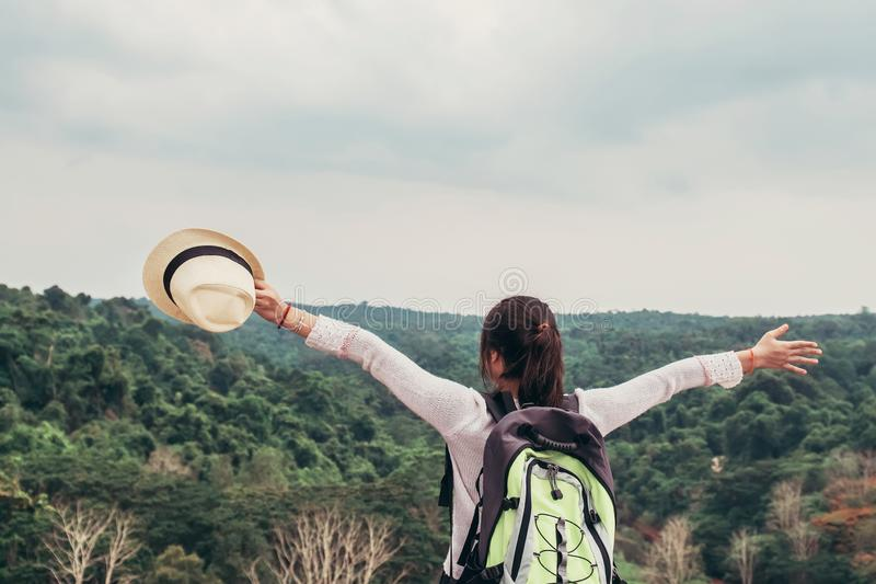 young asian woman traveler with backpack relaxing on mountian and looking forest stock photo