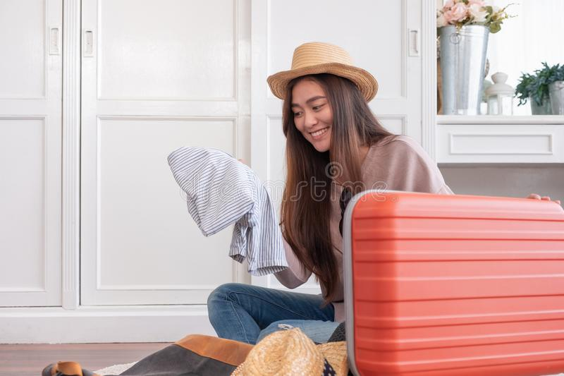 Young asian woman traveler prepare cloth into orange suitcase for holiday vacation at home.backpacker travel concept. royalty free stock image