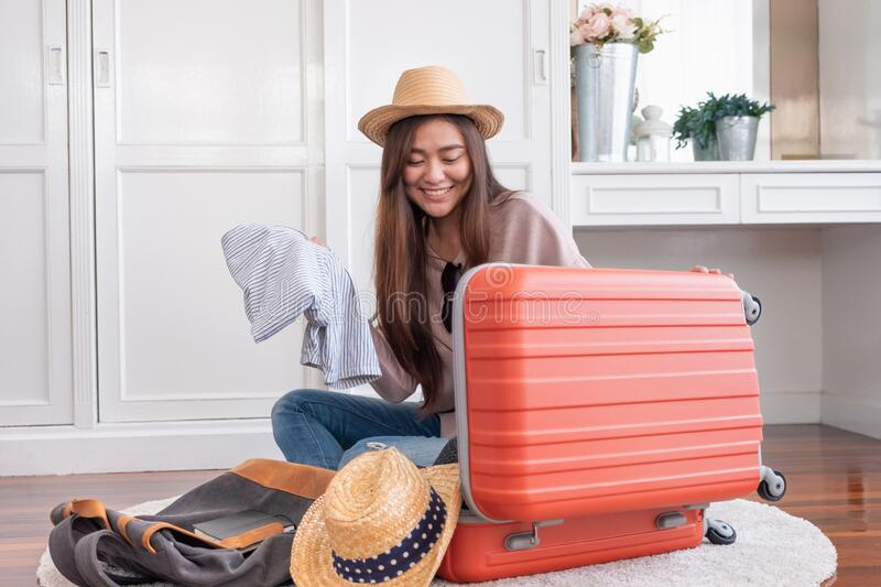 Young asian woman traveler prepare cloth and stuff into orange suitcase for holiday vacation at home.backpacker travel concept royalty free stock photos