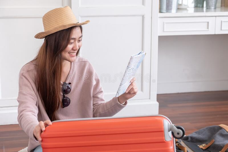 Young asian woman traveler prepare cloth and stuff into orange suitcase for holiday vacation at home.backpacker travel concept stock photography