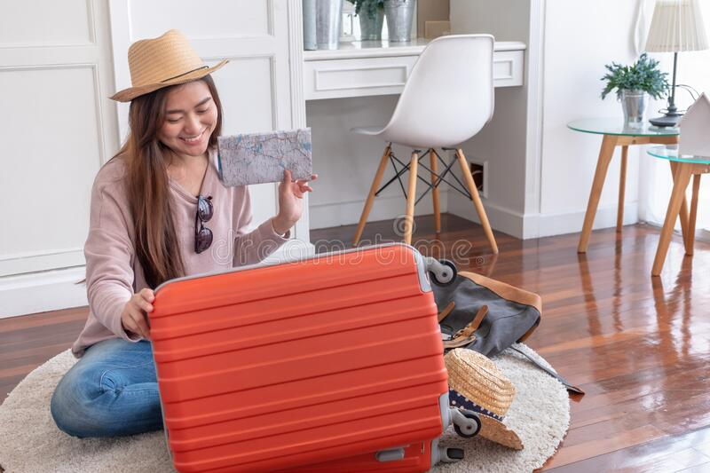 Young asian woman traveler prepare cloth and stuff into orange suitcase for holiday vacation at home.backpacker travel concept stock photos