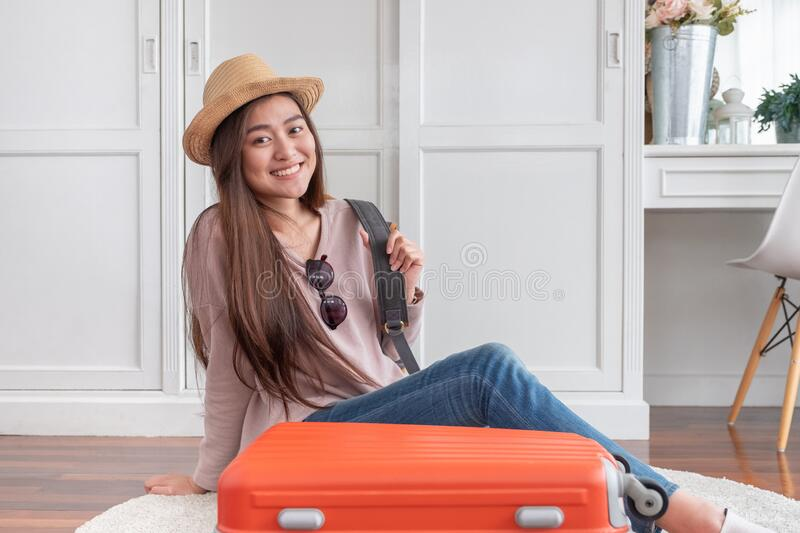 Young asian woman traveler prepare cloth and stuff into orange suitcase for holiday vacation at home.backpacker travel concept royalty free stock image