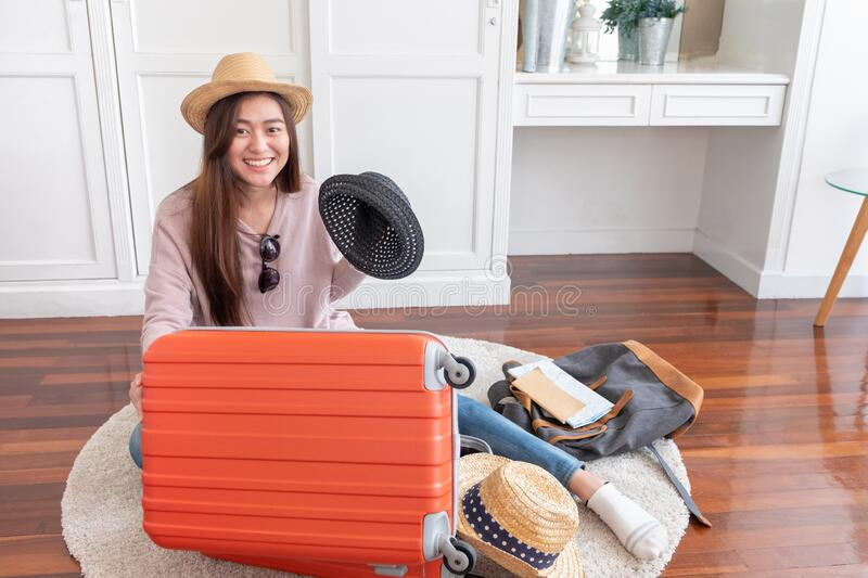 Young asian woman traveler prepare cloth and stuff into orange suitcase for holiday vacation at home.backpacker travel concept royalty free stock photography