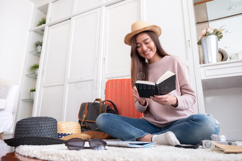 Young asian woman traveler prepare cloth and stuff into orange suitcase for holiday vacation at home.backpacker travel concept stock photo