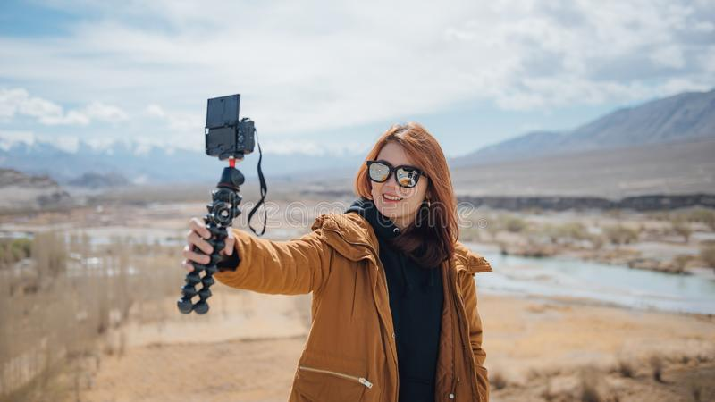 Young asian woman traveler selfie with beautiful mountain between a vacation in leh. royalty free stock images