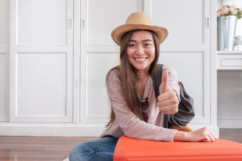 Young asian woman traveler thumbs up with orange suitcase prepare for holiday vacation at home.backpacker travel concept. royalty free stock photos