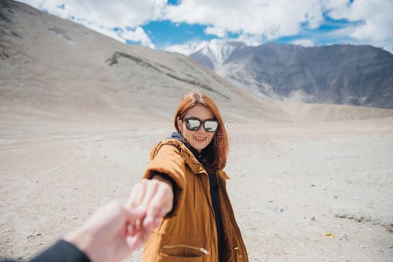 Young asian woman traveler holding man by hand and going to the mountain. stock photography