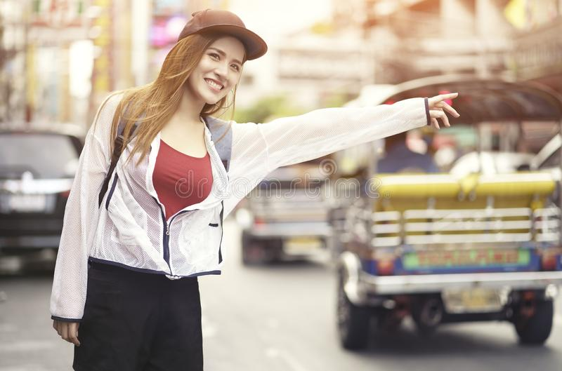 Young asian woman traveling backpacker hailing taxi on street at Yaowarat road outdoor market in Bangkok, Thailand Chinatown royalty free stock image