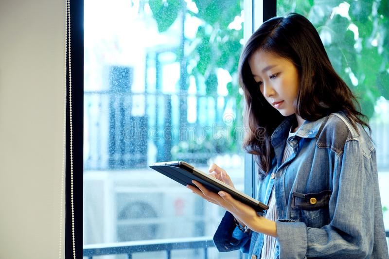 Young asian woman using digital tablet while standing by window at home office background, casual office life, working at home, royalty free stock photo