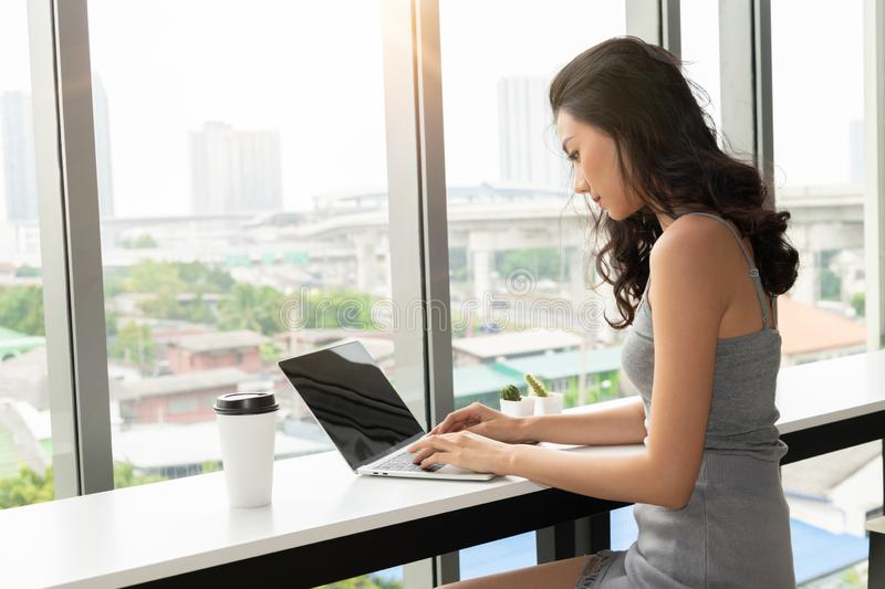 Young asian woman using laptop computer in coffee shop, Include clipping path of screen.  stock photography