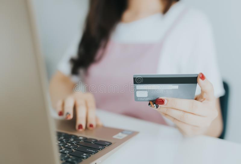 Young asian woman using laptop computer and holding credit card at home. Online shopping and browsing concept royalty free stock images