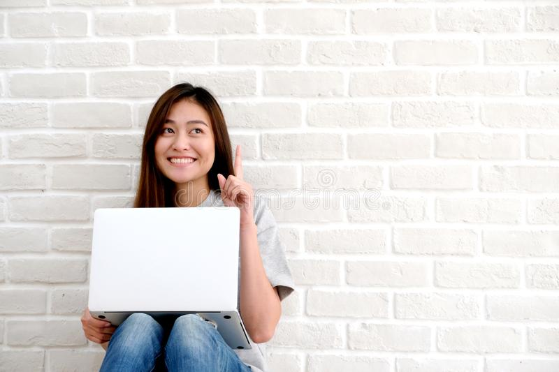 Young asian woman using laptop computer sitting in front of whit royalty free stock photos