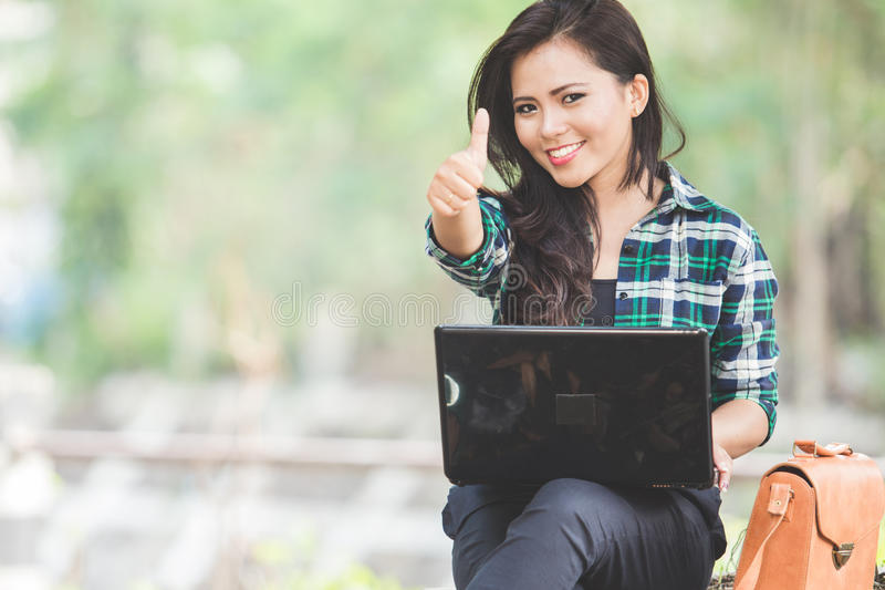 Young asian woman using laptop while sitting on the park. A portrait of a young asian woman using laptop while sitting on the park and showing thumb up stock photos