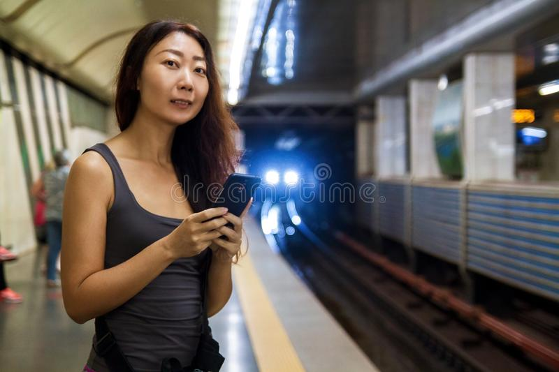 Young asian woman using mobile phone at train station. Young beautiful asian woman using mobile phone at train station stock photo