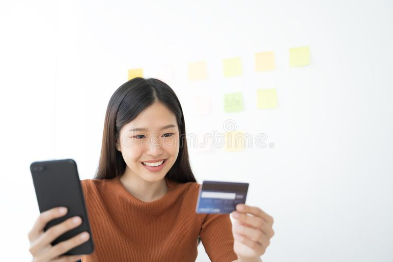 Young Asian woman using smartphone and credit card. Shopping buying online. Young Asian woman using smartphone and credit card. Shopping buying online stock photos
