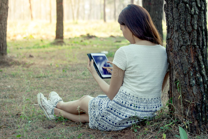 Young asian woman using tablet in the park royalty free stock image