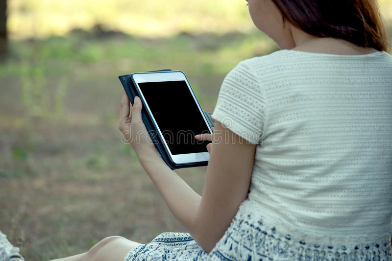 Young asian woman using tablet in the park stock photo