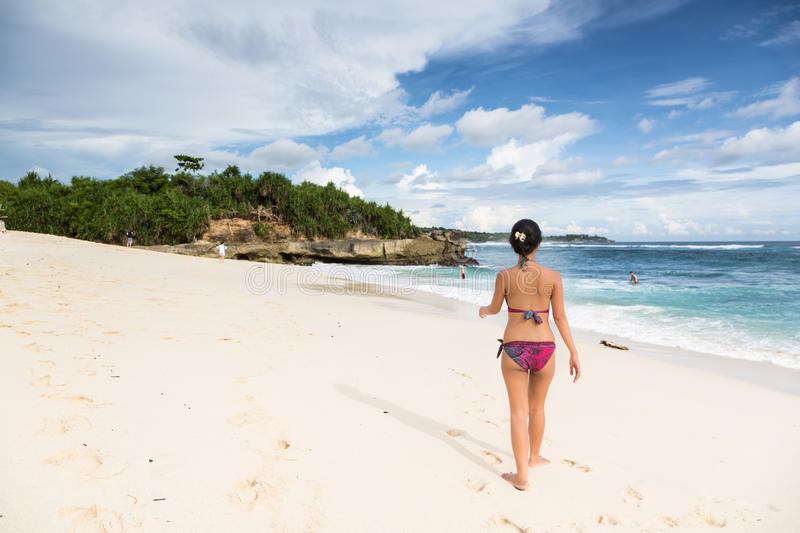 Young Asian woman walking on Lembongan beach in Bali in Indonesia on a sunny day stock photo