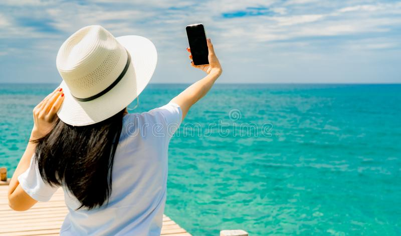 Young Asian woman wear straw hat in casual style use smartphone taking selfie at wooden pier. Summer vacation at tropical paradise stock photography