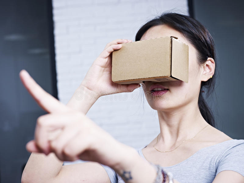 Young asian woman wearing cardboard VR glasses royalty free stock images